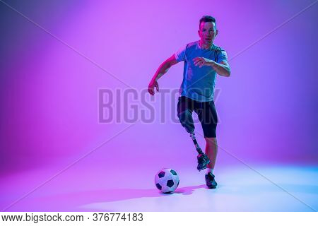 Athlete With Disabilities Or Amputee On Gradient Studio Background In Neon. Professional Male Footba