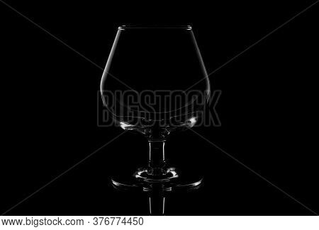 Empty Glass Brandy Glass Isolated On A Black Background.