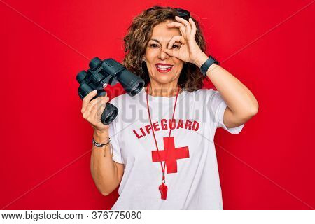 Middle age senior summer lifeguard woman looking through binoculars over red background with happy face smiling doing ok sign with hand on eye looking through fingers
