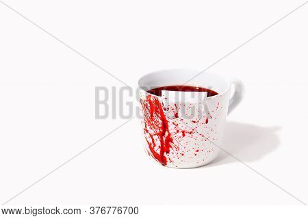White Cup With Fake Blood Splatter And Toy Dracula Teeth On White Background With Copy Space. Creati