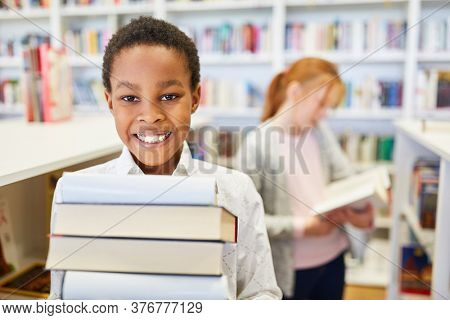 African schoolboy with a stack of books in the library of elementary school