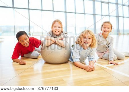 Group of kids in elementary school physical education with a gym ball
