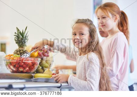 Girls and other children take fruits from the buffet in elementary school