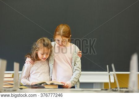 Two girls as elementary school students learn to read together in the classroom