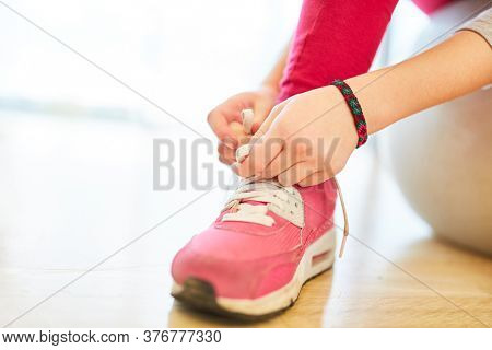 Child in elementary school physical education ties her shoes