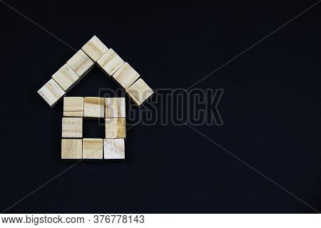 A House Of Wooden Blocks On A Dark Background. The  The Concept Of Real Estate, House Building, Insu