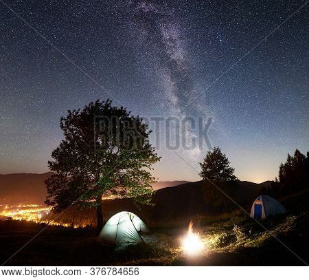 Tourist Camping Near Big Tree At Night. Two Tents And Bonfire Under Amazing Night Sky Full Of Stars
