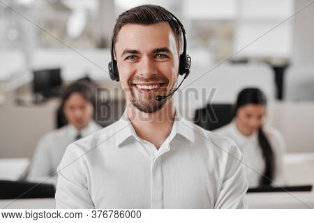 Friendly Man With Headset Smiling And Looking At Camera While Working In Office Of Help Line Of Mode
