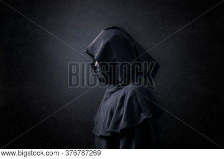 Scary figure in hooded cloak in the dark