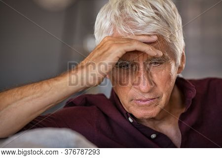 Frustrated senior man with hand on head sitting on couch at home. Stressed retired man suffering alzeheimer alone at home. Worried senior man with terrible headache or migraine.