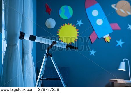 Telescope on tripod in kid's room at night. Telescope standing in child bedroom near the window with the wall decorated with cardboard rocket and solar system. Interior child room with planets, stars.