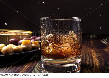 Whiskey With Ice Sprinkled From A Glass. Snack For Whiskey: Pickled Mushrooms Champignons, Olives An
