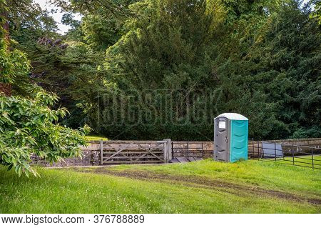 A Plastic Portable Toilet Next To A Muddy Track In A Field At An Outdoor Event And Surrounded By Tal