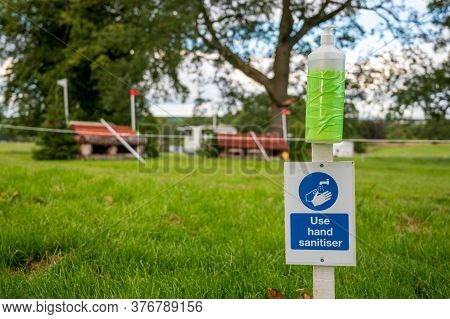Hand Sanitiser And Covid-19 Reminder Sign At An Outdoor Horse Trials Event. Out Of Focus Horse Jumps