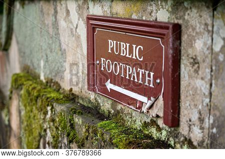 An Old Distressed Public Footpath Sign On A Moss Covered Old Stone Wall.