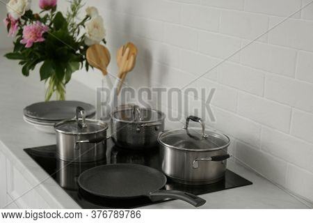 Saucepots And Crepe Pan On Induction Stove In Kitchen