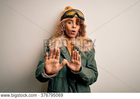 Young african american skier woman with curly hair wearing snow sportswear and ski goggles Moving away hands palms showing refusal and denial with afraid and disgusting expression. Stop and forbidden.