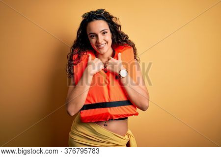 Young beautiful woman with curly hair wearing orange lifejacket over yellow background happy face smiling with crossed arms looking at the camera. Positive person.