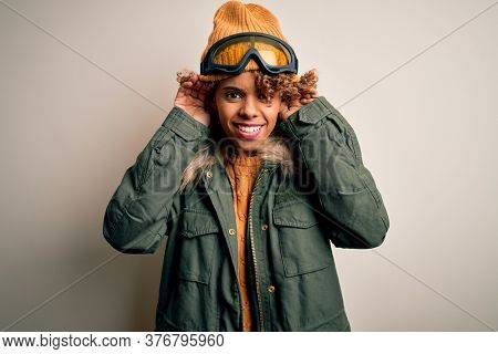Young african american skier woman with curly hair wearing snow sportswear and ski goggles Trying to hear both hands on ear gesture, curious for gossip. Hearing problem, deaf