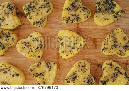 Polenta With Herbs Cut In Heart Shape Placed On Wooden Board