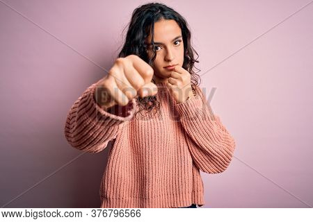 Young beautiful woman with curly hair wearing casual sweater over isolated pink background Punching fist to fight, aggressive and angry attack, threat and violence