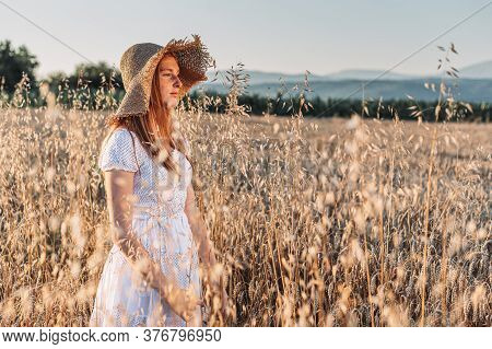 Portrait Of Young, Teen, Ginger Girl With Freckles In The Wheat Field Wearing A Summer Hat. Copy Spa