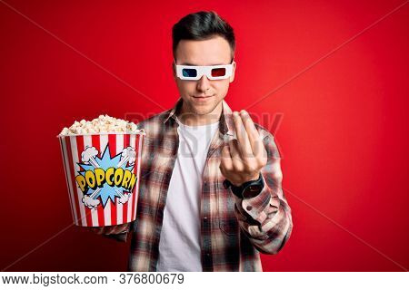 Young handsome caucasian man wearing 3d movie glasses and eating popcorn doing money gesture with hands, asking for salary payment, millionaire business
