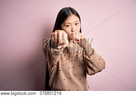Young beautiful asian woman wearing fashion and elegant sweater over pink solated background Punching fist to fight, aggressive and angry attack, threat and violence