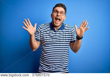 Young man with blue eyes wearing glasses and casual striped t-shirt over blue background celebrating crazy and amazed for success with arms raised and open eyes screaming excited. Winner concept