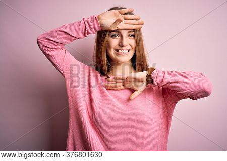 Young beautiful redhead woman wearing casual sweater over isolated pink background Smiling cheerful playing peek a boo with hands showing face. Surprised and exited