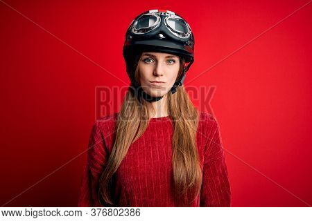 Young beautiful redhead motocyclist woman wearing moto helmet over red background with serious expression on face. Simple and natural looking at the camera.