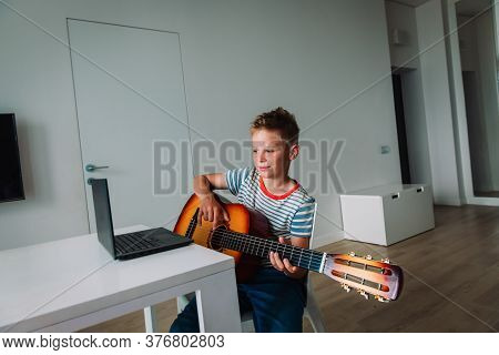 Kid Having Guitar Lesson Online, Remote Music Class