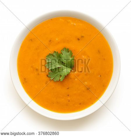 Carrot And Coriander Soup With Fresh Coriander Garnish In A White Ceramic Bowl Isolated On White. To