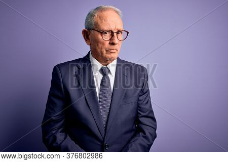 Grey haired senior business man wearing glasses and elegant suit and tie over purple background skeptic and nervous, frowning upset because of problem. Negative person.
