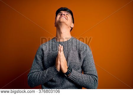 Young handsome man wearing casual sweater standing over isolated orange background begging and praying with hands together with hope expression on face very emotional and worried. Begging.