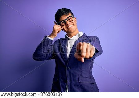 Young handsome business man wearing jacket and glasses over isolated purple background smiling doing talking on the telephone gesture and pointing to you. Call me.
