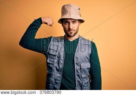 Handsome tourist man with beard on vacation wearing explorer hat over yellow background Strong person showing arm muscle, confident and proud of power