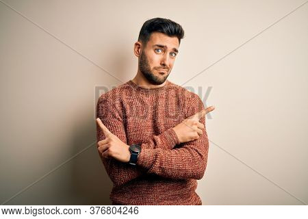 Young handsome man wearing casual sweater standing over isolated white background Pointing to both sides with fingers, different direction disagree