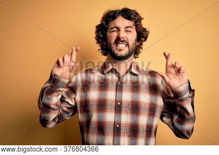 Young handsome man with beard wearing casual shirt standing over yellow background gesturing finger crossed smiling with hope and eyes closed. Luck and superstitious concept.