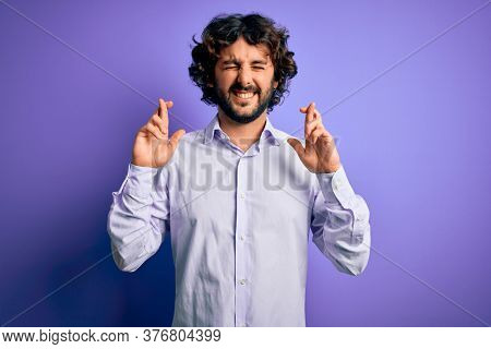 Young handsome business man with beard wearing shirt standing over purple background gesturing finger crossed smiling with hope and eyes closed. Luck and superstitious concept.
