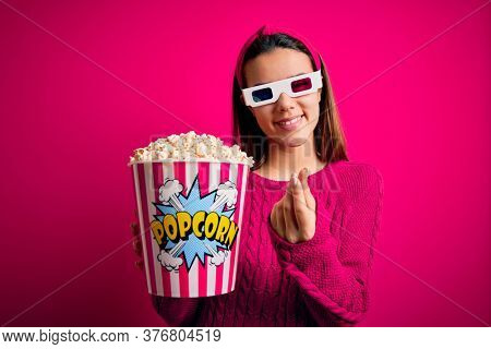 Young beautiful girl watching movie using 3d glasses eating box with popcorns doing money gesture with hands, asking for salary payment, millionaire business