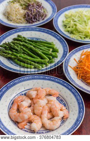 Prawns, Green Asparagus, Carrots, Iceberg Lettuce And Alfalfa On A Wooden Table