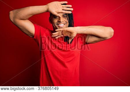 Young handsome african american afro man with dreadlocks wearing red casual t-shirt Smiling cheerful playing peek a boo with hands showing face. Surprised and exited