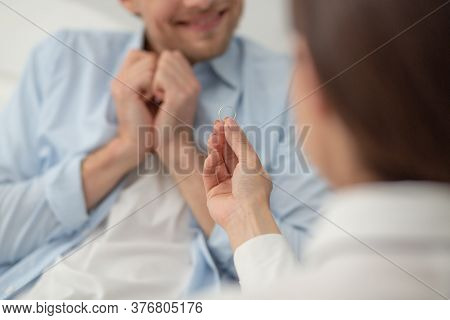 Females Hand Holding Engagement Ring Proposing. Woman Doing Marriage Proposal To Her Boyfriend And H