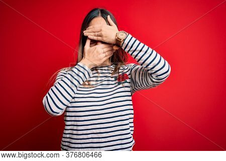 Young beautiful blonde woman with blue eyes wearing glasses standing over red background Covering eyes and mouth with hands, surprised and shocked. Hiding emotion