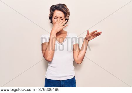 Young beautiful woman wearing casual clothes smelling something stinky and disgusting, intolerable smell, holding breath with fingers on nose. bad smell