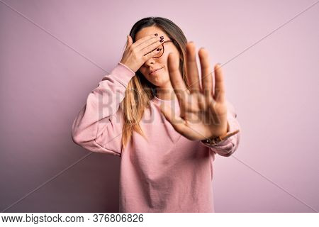 Beautiful blonde woman with blue eyes wearing sweater and glasses over pink background covering eyes with hands and doing stop gesture with sad and fear expression. Embarrassed and negative concept.