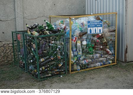Glass And Plastic Bottles In Trash Containers. Sorting And Recycling Garbage Concept. Utilization Co