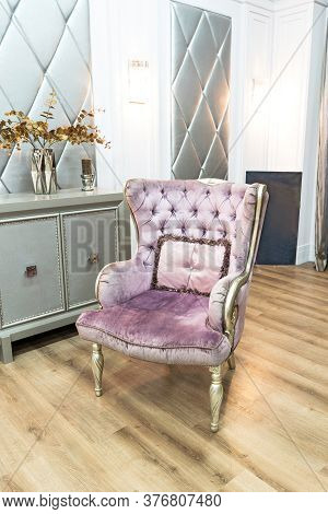 Violet Quilted Armchair In Luxury House Interior With Silver Furniture And Grey Commode. Selective F