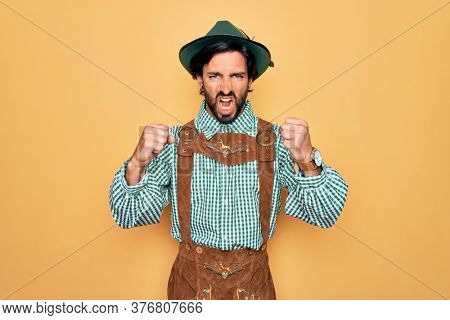 Young handsome man wearing tratidional german octoberfest custome for Germany festival angry and mad raising fists frustrated and furious while shouting with anger. Rage and aggressive concept.